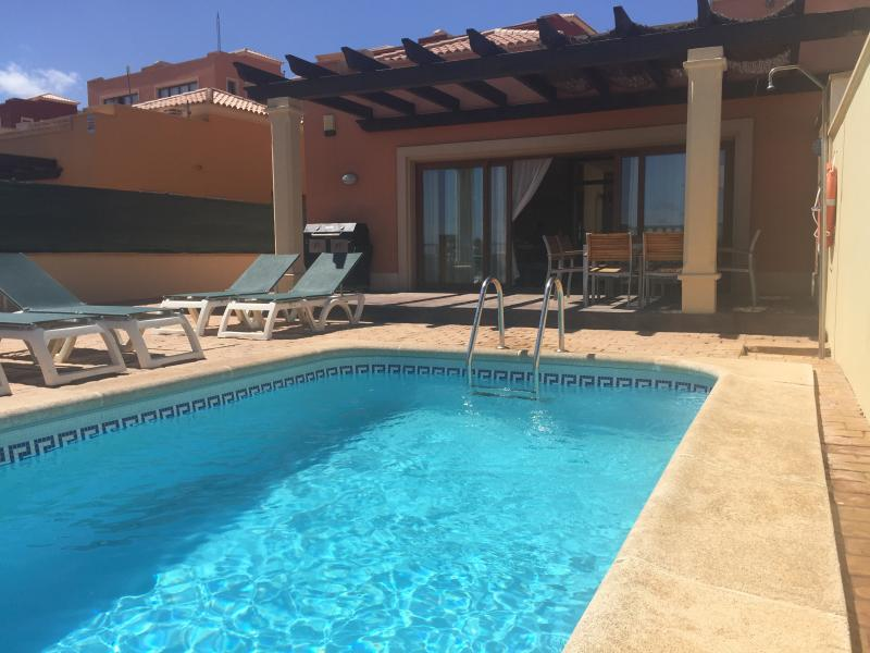 Outside pool area with barbeque, lounge seating, 8 seater dining, sunbeds & pool