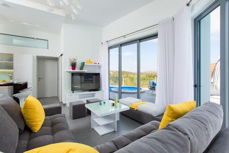 The living room area offers direct access to the pool and terrace!