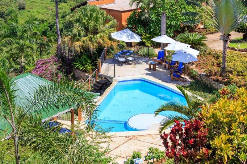 The residence has a spacious pool area with lounge chairs and a barbeque.