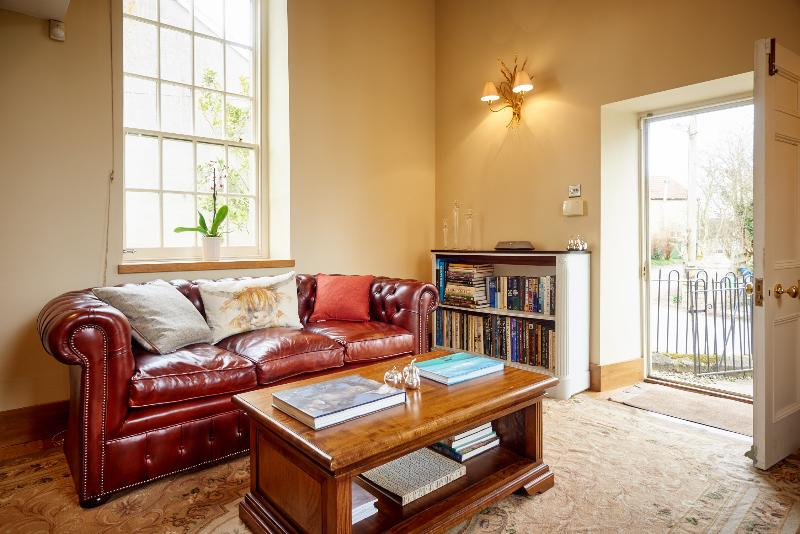 The stylish living area has plenty of comfortable furnishings, a wood burning stove & exposed beams.