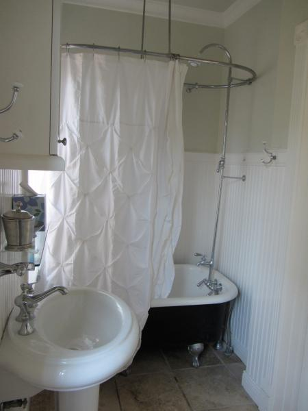 Clawfoot tub with showered attachment.