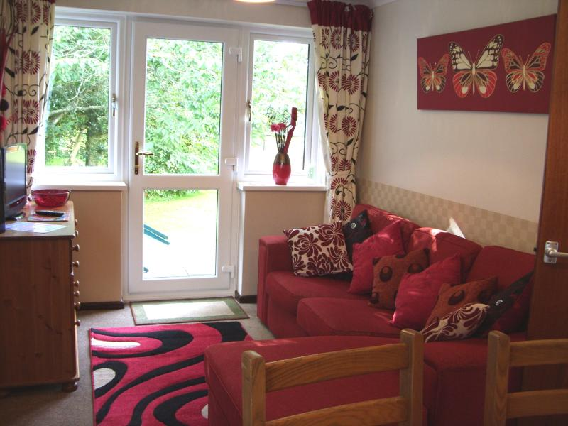This is the living area with a large sofa with large sunshine windows for that added light.
