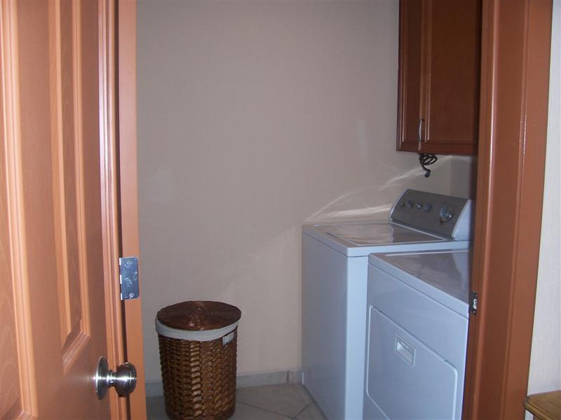 Laundry room with sink, ironing board, full sized washer and dryer