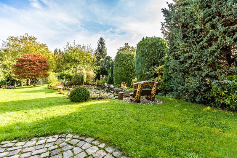 Wunderschöner Garten mit großem Teich und Gartenbank direkt vor der Apartmenttüre