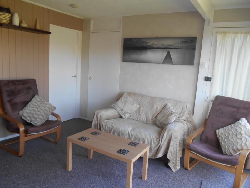 Lounge sitting area including two seater sofa and comfortable occasional chairs with coffee table