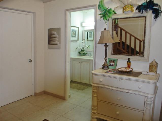 entrance foyer with full bathroom, and utility area with mahogany staircase leading up to main floor