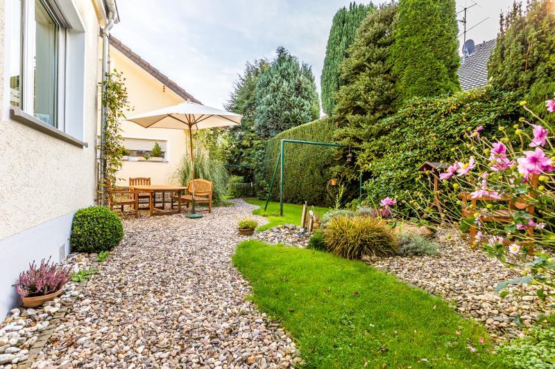 Blick in den Garten mit schönem Sitzplatz und kleinem Gartenteich
