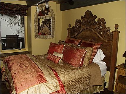 The queen in the master bedroom has a beautiful and ornate carved wood bed.