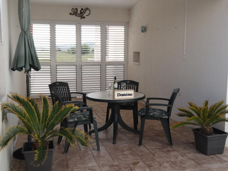 Covered outdoor dining/games area with dart board.