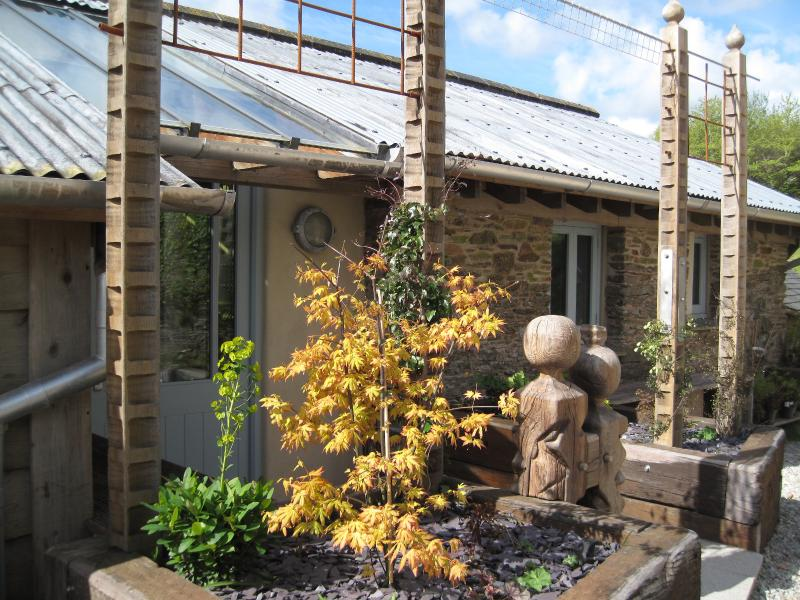 The entrance to The Piggery with carved oak posts and Clematis..  Art and light inside and out..