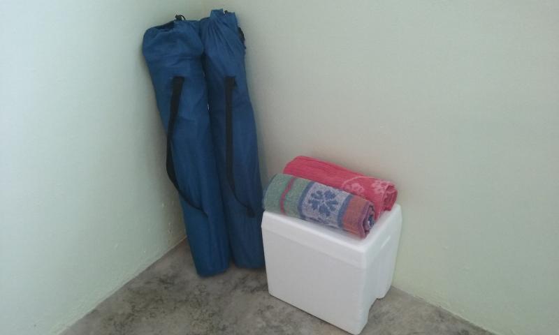 Duas cadeiras de praia, toalhas e um refrigerador estão aguardando sua chegada.