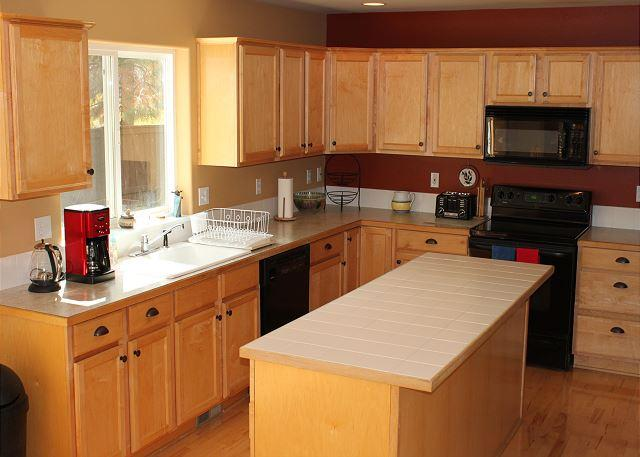 Well-stocked kitchen with electric stove and all appliances