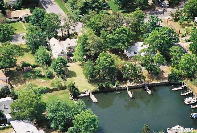 Aerial view of home and yard and dock on protected canal.