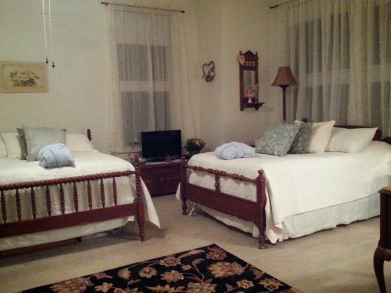 Grote voorste slaapkamer met twee tweepersoonsbedden en flatscreen kabel-TV