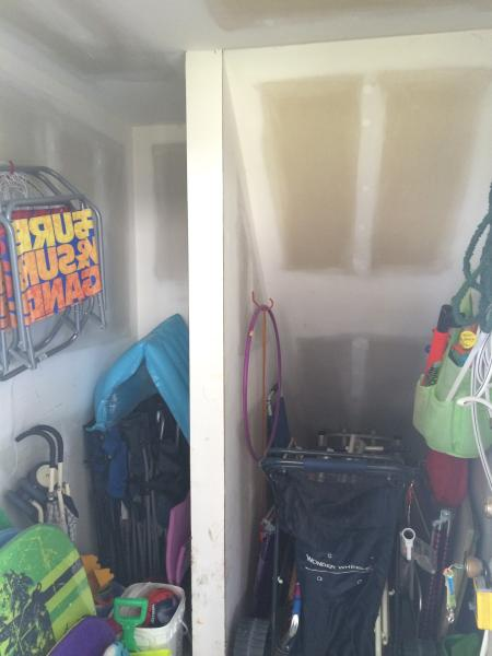 Storage room with beach chairs, umbrella, toys, and cart.