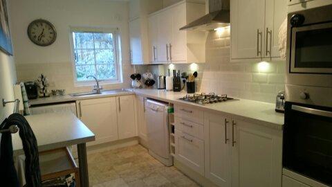 A luz cozinha com superfícies de trabalho bom, máquina de lavar-secar roupa e máquina de lavar louça