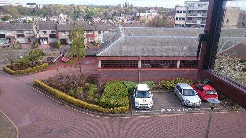 Garagem com estacionamento para apartamentos e espaços extras fora, como pode ser visto da janela do quarto