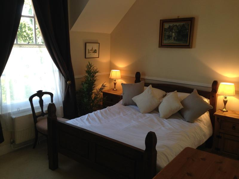 Master bedroom with king size bed at Clewer lodge in whitstable