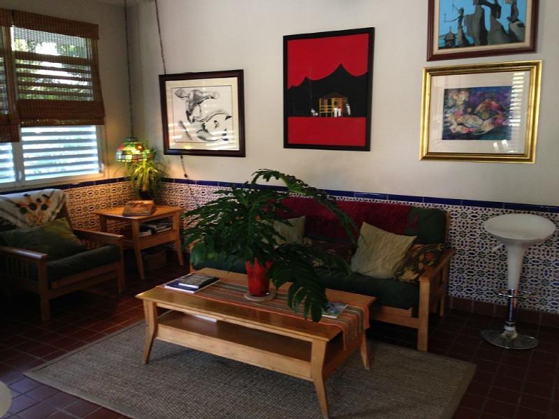 Sala de estar con techos de 10 pies de alto y hermosas obras de arte para estimular gran relajación w/brisa!