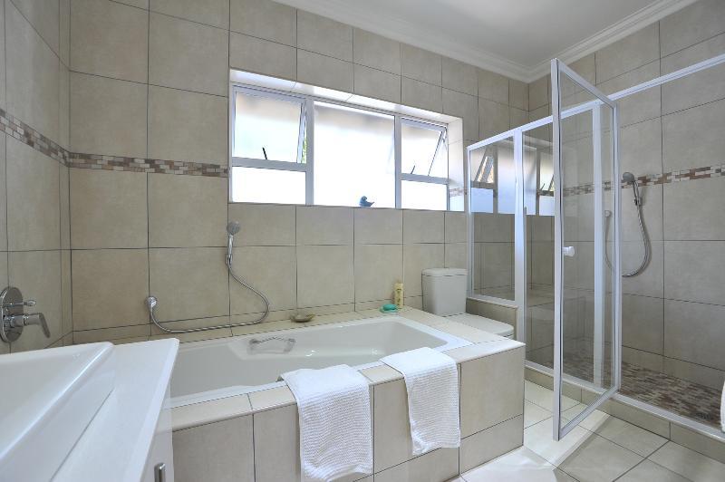 Salle de bains avec baignoire et promenade dans la douche