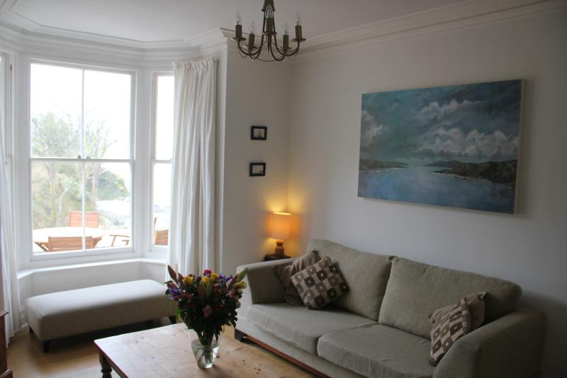 Sitting room, view towards the bay window, patio and sea beyond.