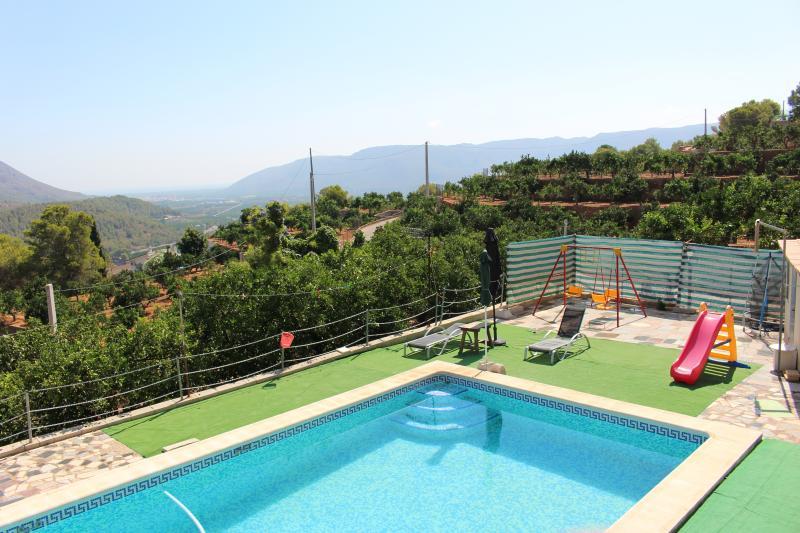 Vista de la piscina desde el chalet, zona columpios.