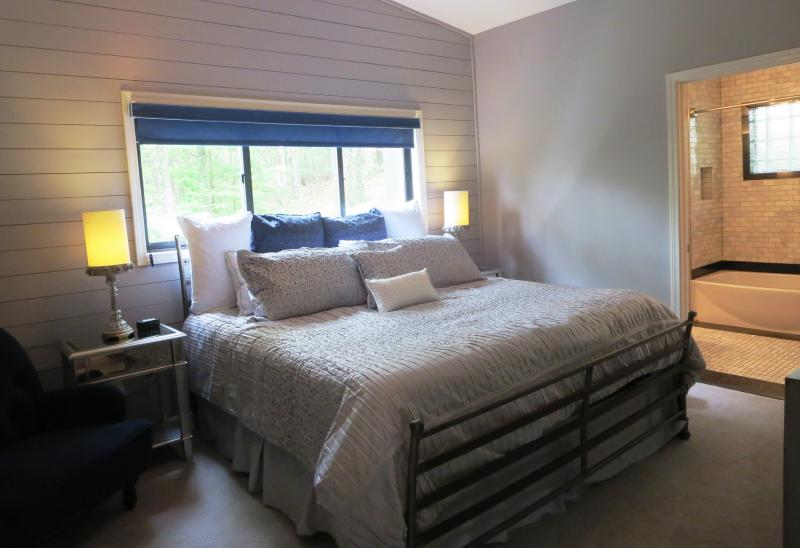 The first master bedroom has a king size bed and space for reading & watching tv.