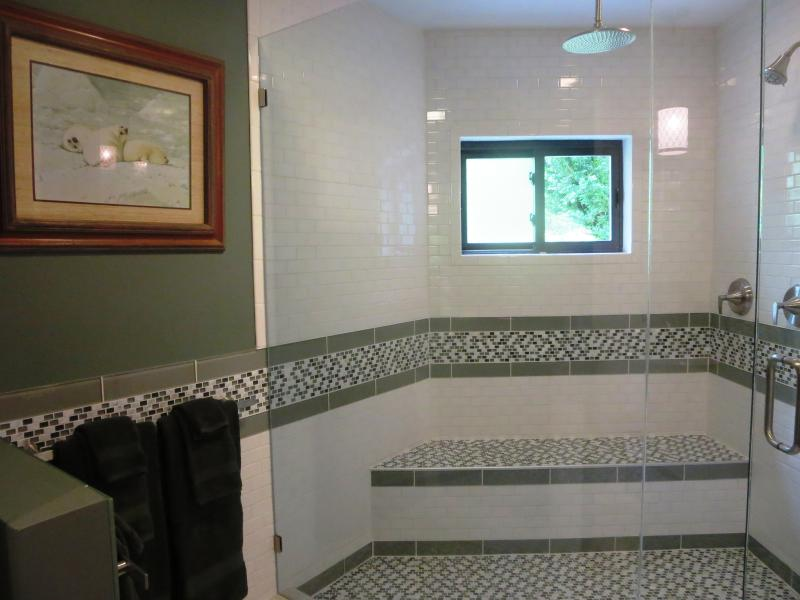 This walk in shower with rainfall shower head & bench seat is gigantic.