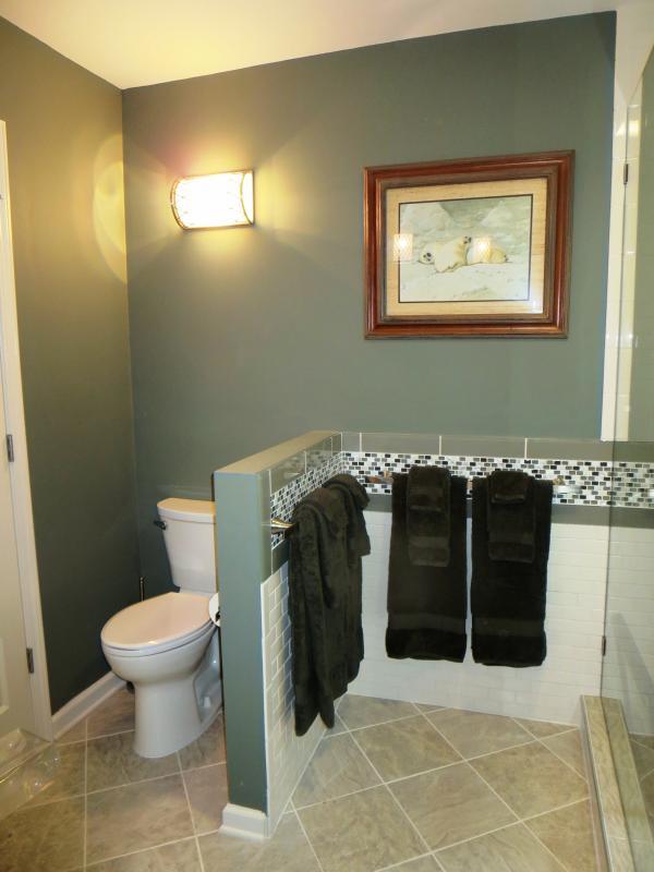 The glass mosaic tile wraps around the bath.
