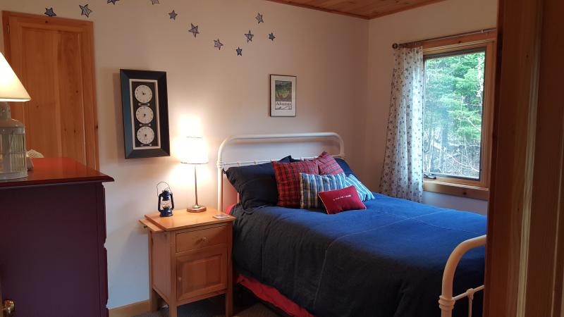 One of two main floor bedrooms, this one looks out at a large stand of trees, very pretty.
