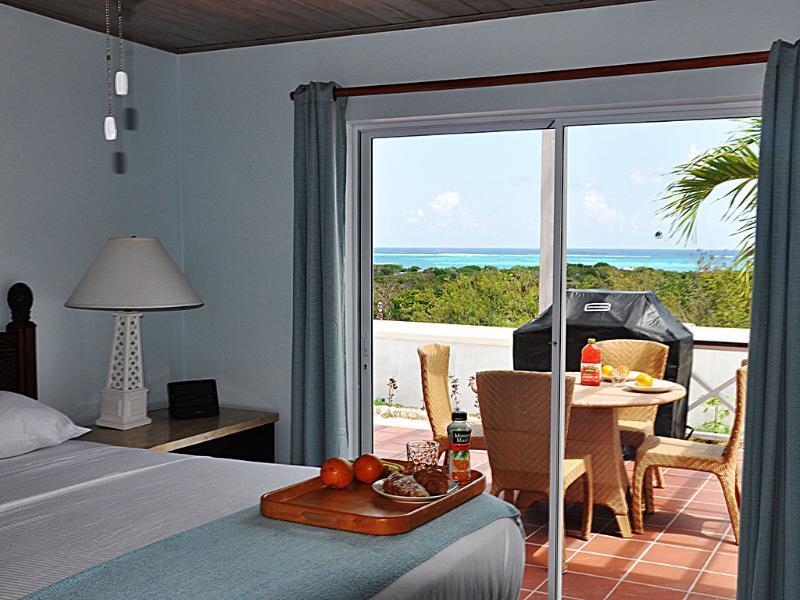 Master bedroom in two bedroom villa, overlooking patio and ocean