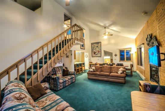 Spacious Living Area with Vaulted Ceilings, Gas Fireplace, and Deck Access