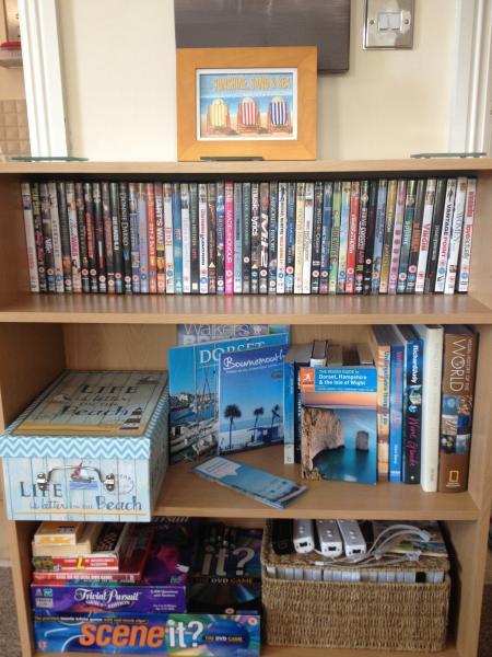 Libreria con i DVD, giochi da tavolo, giochi per Wii e controller, libri e informazioni turistiche locali