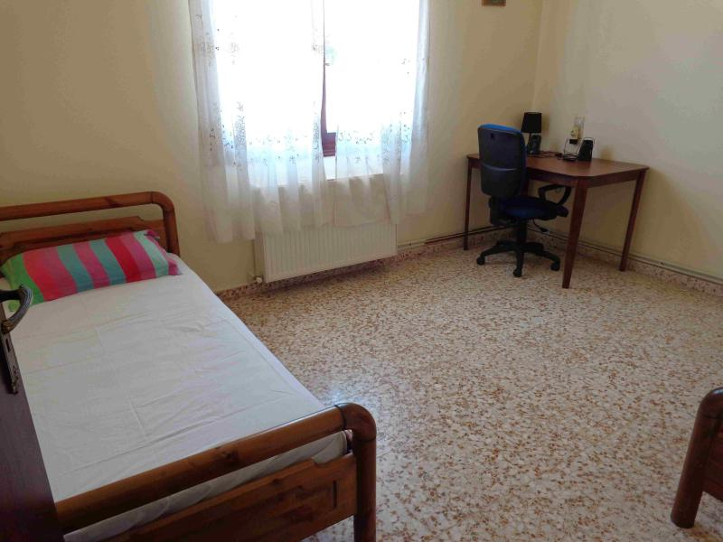 The bedroom with two single beds and a small desk.