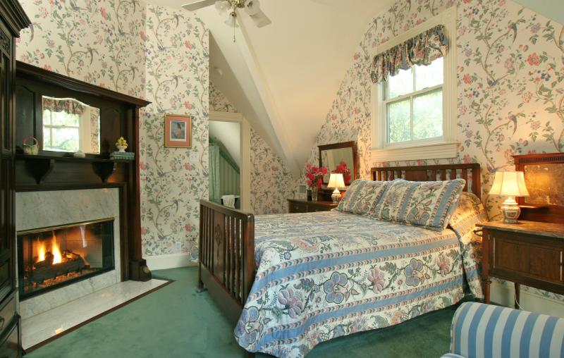 Bedroom with vaulted ceilings and queen size bed. Antique furnishings