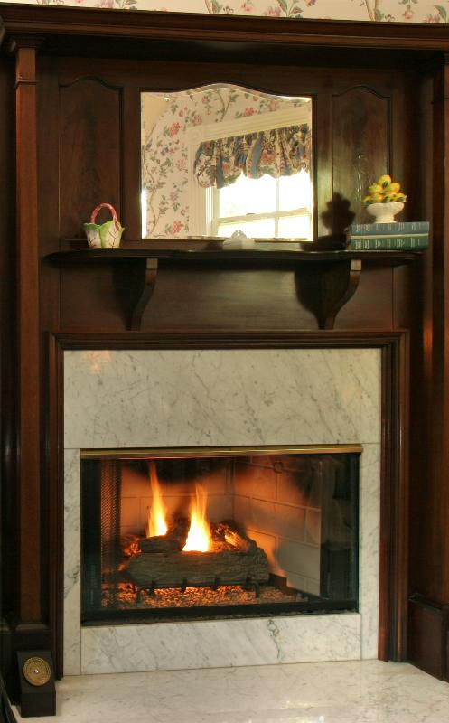 Gas fireplace with antique mantelpiece turns on/off with a flip of a switch