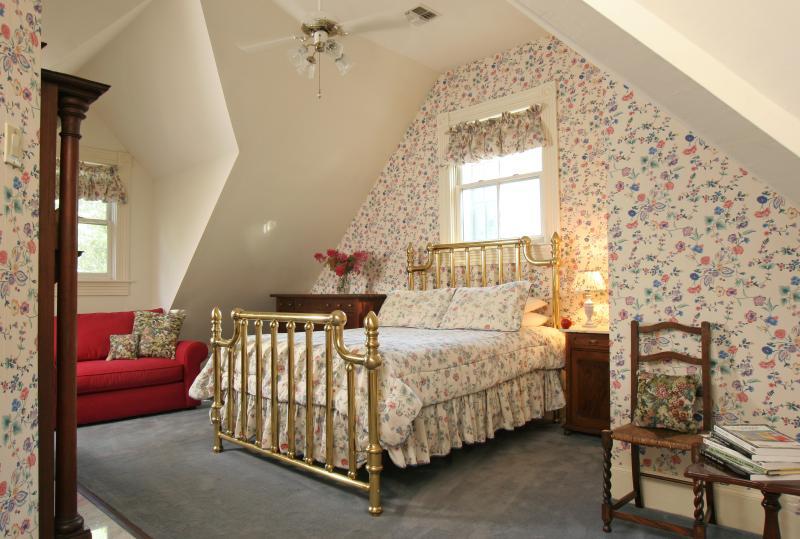 Dormitorio con cama de latón antiguo queen size. Sofá para sentarse es también un sofá cama doble
