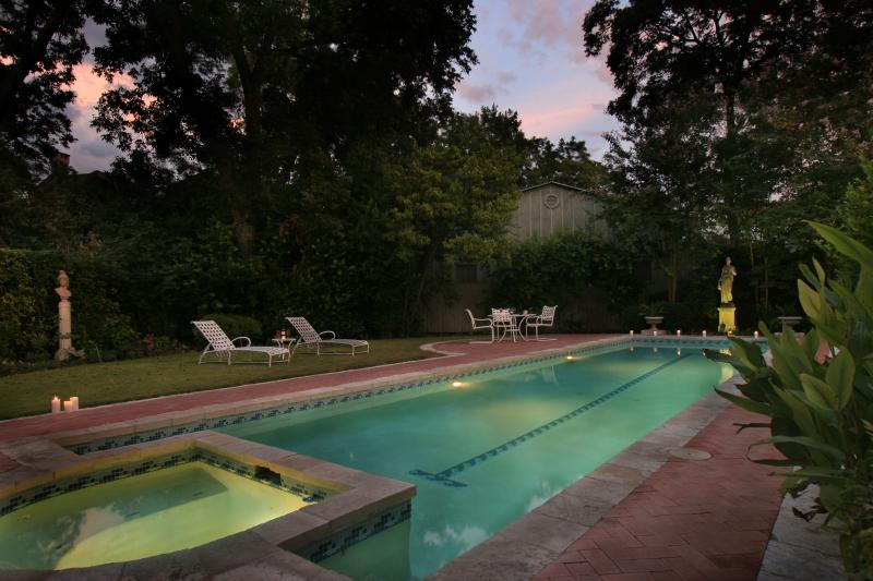 Outdoor pool with heated spa. Patio with chaises, table and chairs. Beautifully lighted at night