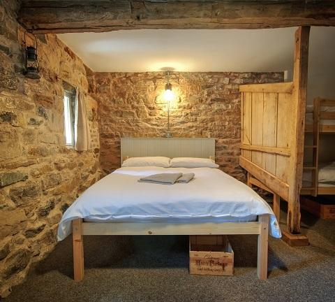 Restored stable stall provides privacy in the bedroom.
