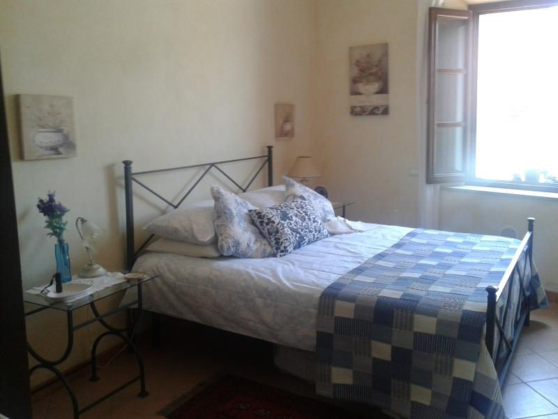 bright large bedroom with window onto the small village