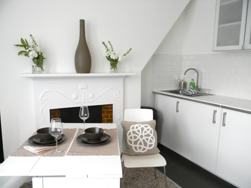 Dining area beside kitchen with original edwardian fireplace in background