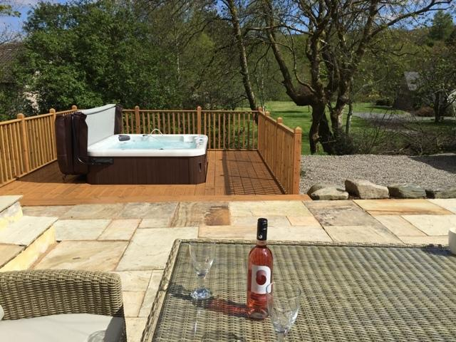 Patio area with table, seating and decking with hot tub