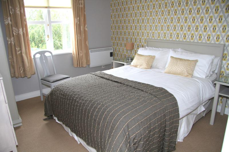 Luxury bed with quality bed linen, wardrobe, chest of drawers, vanity area with mirror.