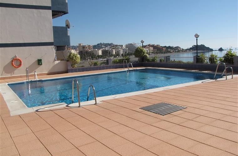 Poser à l'arrière de la piscine avec vue sur la plage de San Cristobal