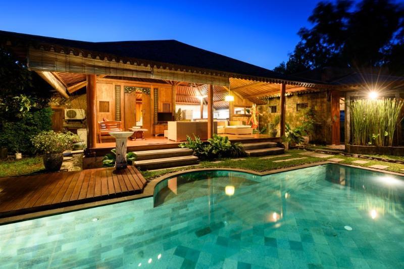 Villa med utsikt över poolen nattetid.