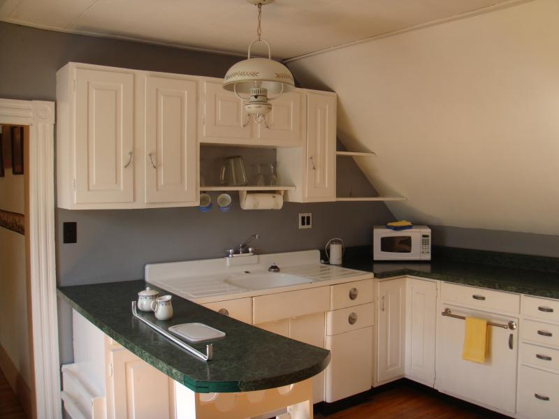 Kitchen with microwave, coffee pot, stove, fridge, and toaster.