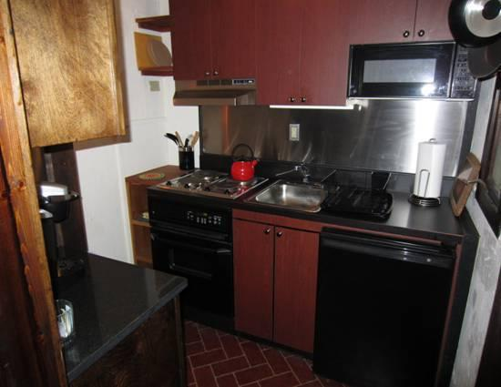 The kitchen with stove, sm refrigerator, microwave, Kurig coffee maker, blender...