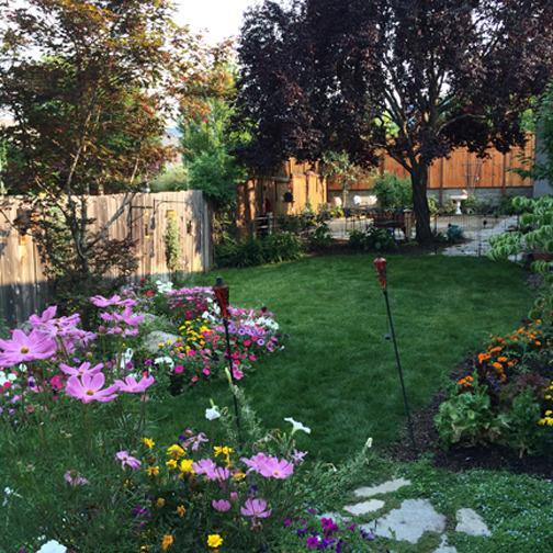 Backyard has beautiful gardens, large sitting area, birds, flowers, pear tree.
