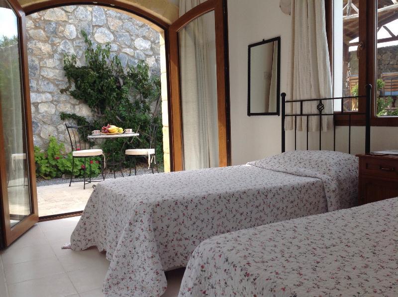 Bedroom 3 twin bed with doors leading to rear garden terrace