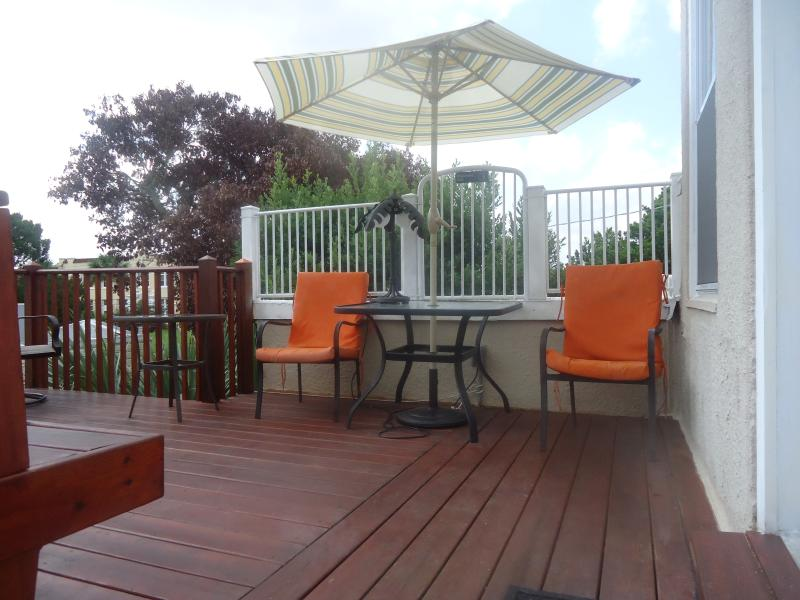 Deck by private entrance to 2nd floor, tables, built-in bench, etc.